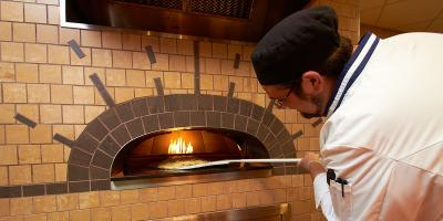 Chef Zach Lorber making pizza in the wood oven