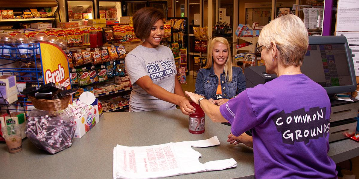 Common Grounds employee and two female students making a purchase