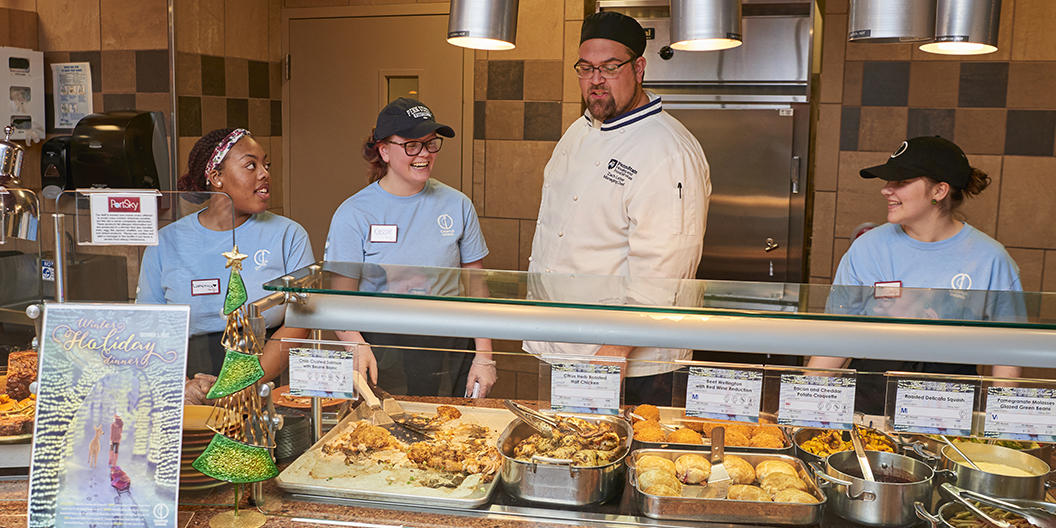 Chef and student employees prepare to serve guests at Port Sky