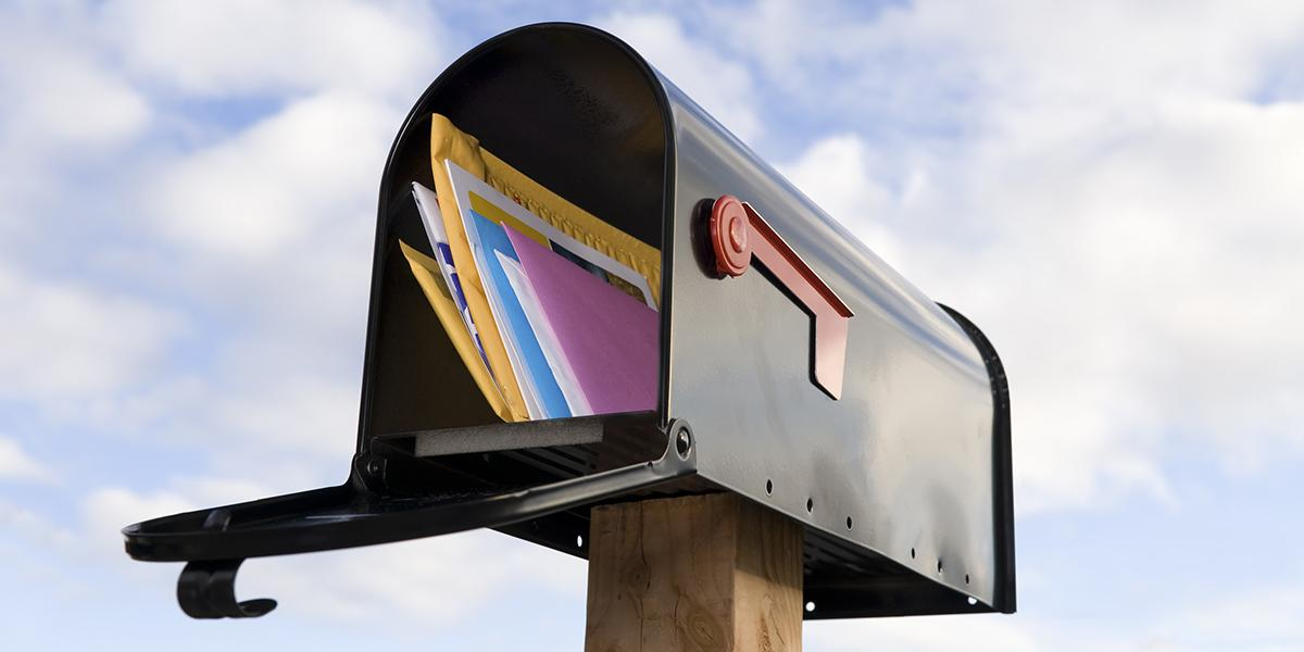 letters in an open mailbox against a cloudy blue sky